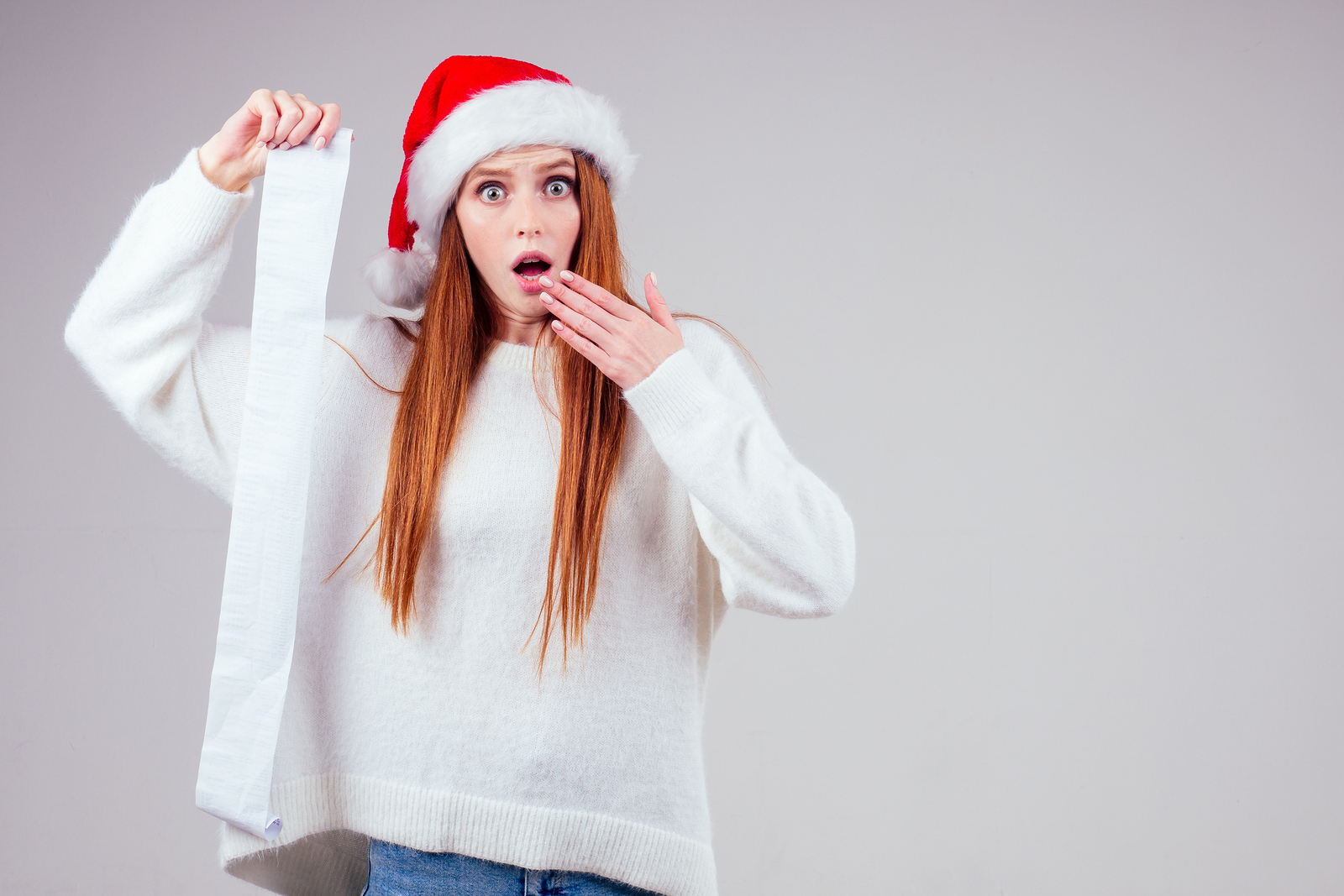 person in Santa Hat holding a long gift list